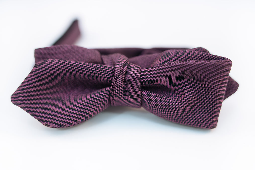 A lustrous 100% virgin wool bow tie with hues of violet and a very light hint of black wool with this two-tone butterfly bow tie. This bow tie is reserved for those who want to distinguish themselves apart from the average wool bow ties and elevate their wardrobe.  100% Virgin Wool. Imported from Italy.  Height: 1.75
