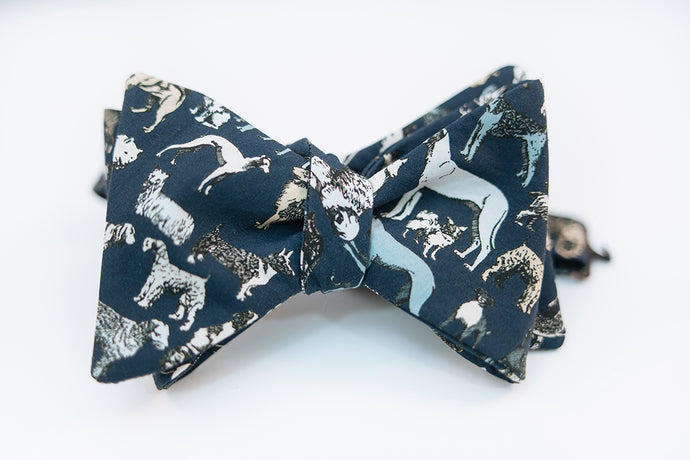 Calling all dog lovers, this lightweight cotton poplin bow tie with dog print on a navy background is the ultimate way to show your love for your favorite pup.   Height: 3