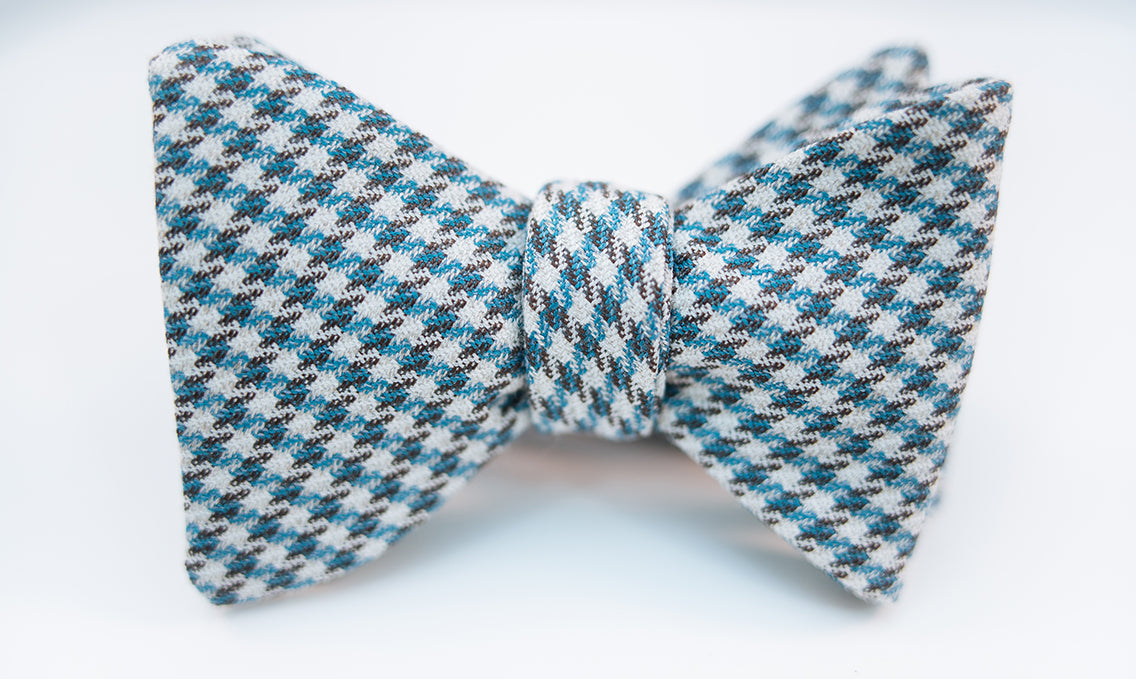 The Hildebrand is Italian silk and wool blend bow tie with a houndstooth design. This soft and lightweight bow tie has hues of beige, brown, and a turquoise blue to add the perfect touch.  Imported from Italy.  Height: 3