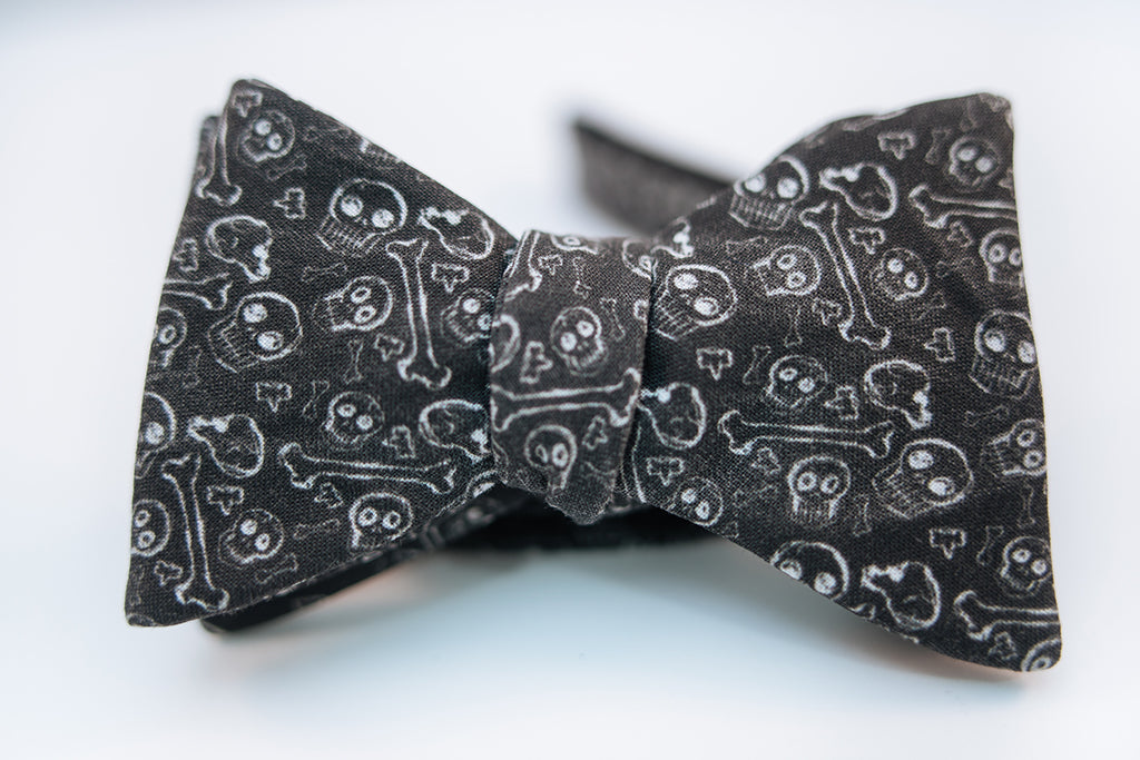 "A black cotton bow tie with white printed designs of skulls and bones on this bold and rebellious bow tie.  Height: 1.75"" x Width:5"
