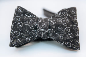 "A black cotton bow tie with white printed designs of skulls and bones on this bold and rebellious bow tie.  Height: 1.75"" x Width:5""   Knot Size: .75""  (Approx.)  Dry Clean Only"
