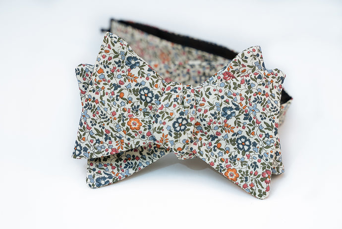 A lightweight cotton lawn bow tie hoast an array of spring forward hues like orange, light and dark blues and rosy red floral petals. This floral pattern is laying on a neutral beige solid background, perfect for any light and pastel shirts for the warmer weather to come.   Height: 3