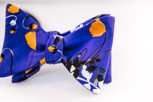 Liberty Of London Cotton Bow Tie With A Poppy Floral Design. A Orange Poppy dances on a solid blue background and abstract black and white floral patterns to tone down this traditional butterfly design.