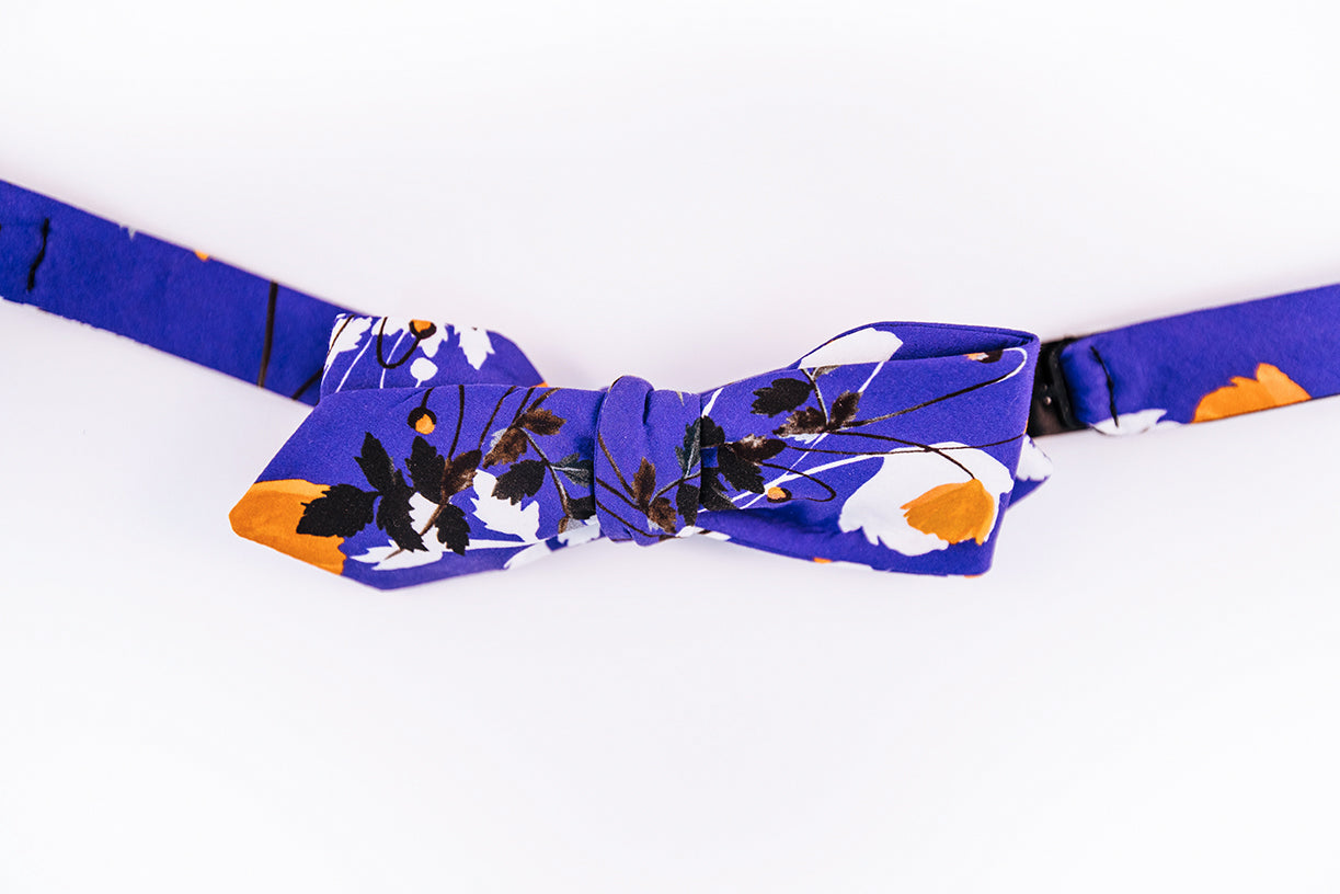 Liberty Of London Cotton Bow Tie With A Poppy Floral Design. A Orange Poppy dances on a solid blue background and abstract black and white floral patterns to tone down this bold slim diamond tip design.