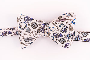 A array of musical instruments dancing on a solid beige background. Hosting instruments from violins, to snare drums, maracas, and many other brass instruments on this cotton butterfly bow tie.