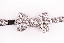 black skulls and bones pattern on this white cotton bow tie with a butterfly design.