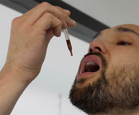 A man takes deer antler velvet by inserting liquid drops under his tongue.