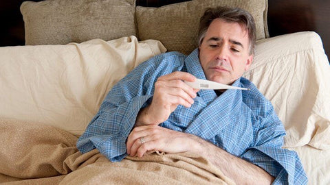 dad sick in bed with thermometer