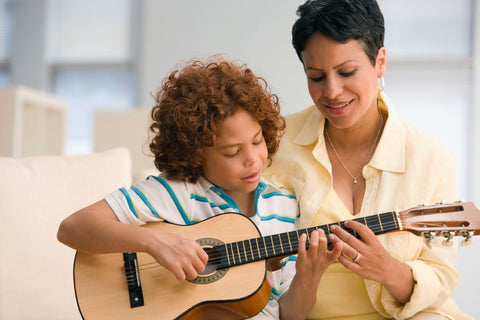 mom helping son play the guitar