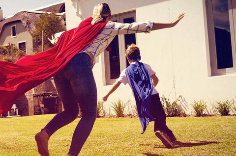 mom and son playing outside with capes