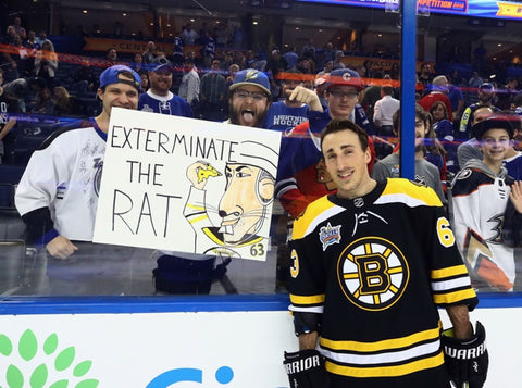 "Brad Marchand standing in front of disgruntled fans with sign saying ""Exterminate The Rat"""