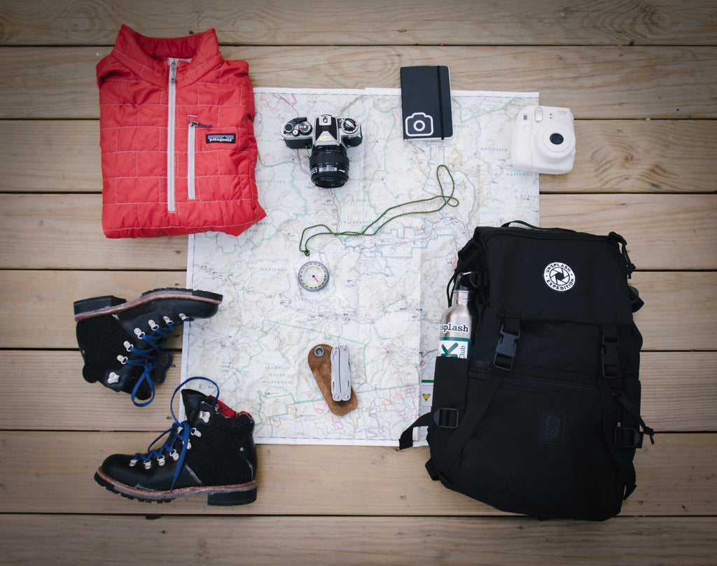 Image of travel necessities including jacket, boots, map, camera, backpack, compass