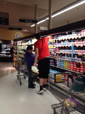 tall person helping short person with top shelf