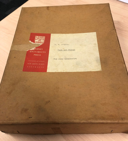 Colour photo of a brown cardboard box about the size of an A4 page. The box shows sign of age and affixed to it is a red and white sticker displaying the SUP logo and the typewritten words: WM O'Neil, Fact and Theory, Top copy typescript.