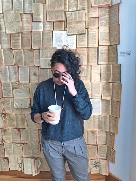 A young woman wearing dark blue jumper and grey trousers standing in front of a wall created out of open books. She is holding a white cup in her right hand, and taking her suglasses off with her left hand.