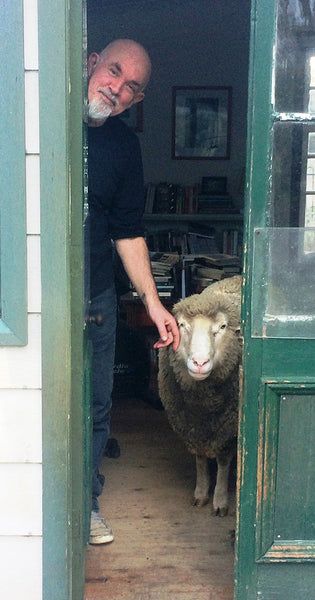 A man with bearded face standing on the left is touching a face of a sheep. Both are visible through an open green door.