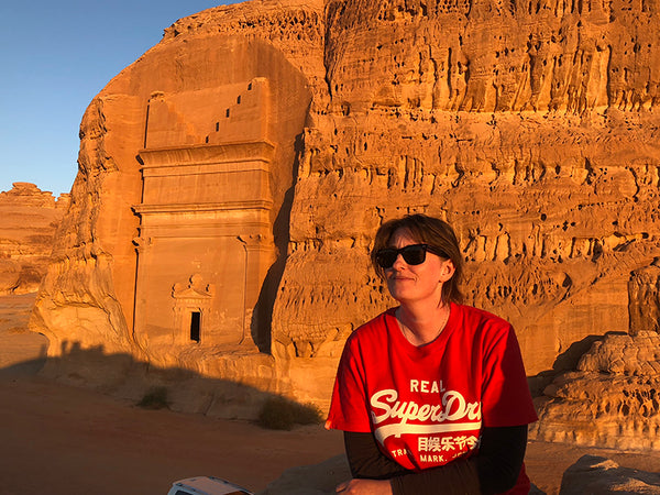 A woman with light brown hair, wearing sun glasses and a red t-shirt with white text, is posing in front of a rock wall with carved entrance to a tomb visible on the left.