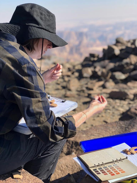 A woman wearing a hat and brown clothing is looking at pottery and a note book with colour swatches, which are lying on the ground. There are blurry mountains in the background.
