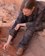 A young woman with light brown hair wearing brown-and-blue checkered shirt and jeans covered in dirt, is shown excavating with a trovel. She is shown seated on the edge of the trench and looking down.