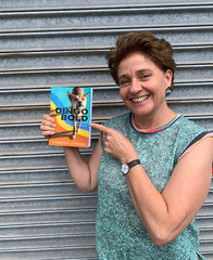 A photo of Rowena Lennox standing in front of a metal door and holding a copy of her book Dingo Bold.