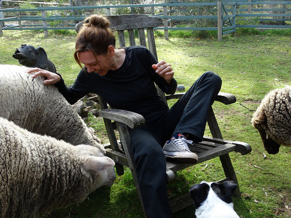 Teya, a woman wearing black t-shirt, dark trousers and white trainers is sitting in a woden chair surrounded by three sheep and a dog.