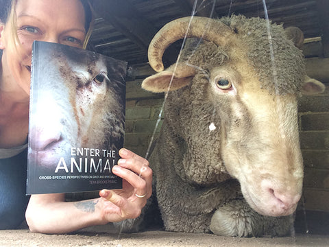 Photo of the heads of Teya and Orpheus-Pumpkin, the sheep. Teya is holding her book Enter the Animal with a photo of sheep's head on the cover. The book obscures most of Teya's head, leaving eyes and the arm visible.