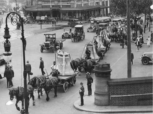 Black and white photo of a wide Sydney street in 1928. Horses pull flat-bed open wagons, carrying large metal bells, as pedestrians look on. A few early 20th century cars pass by.