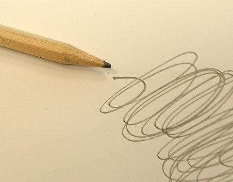 Colour photo of a yellow pencil next to a grey scribble on a piece of paper
