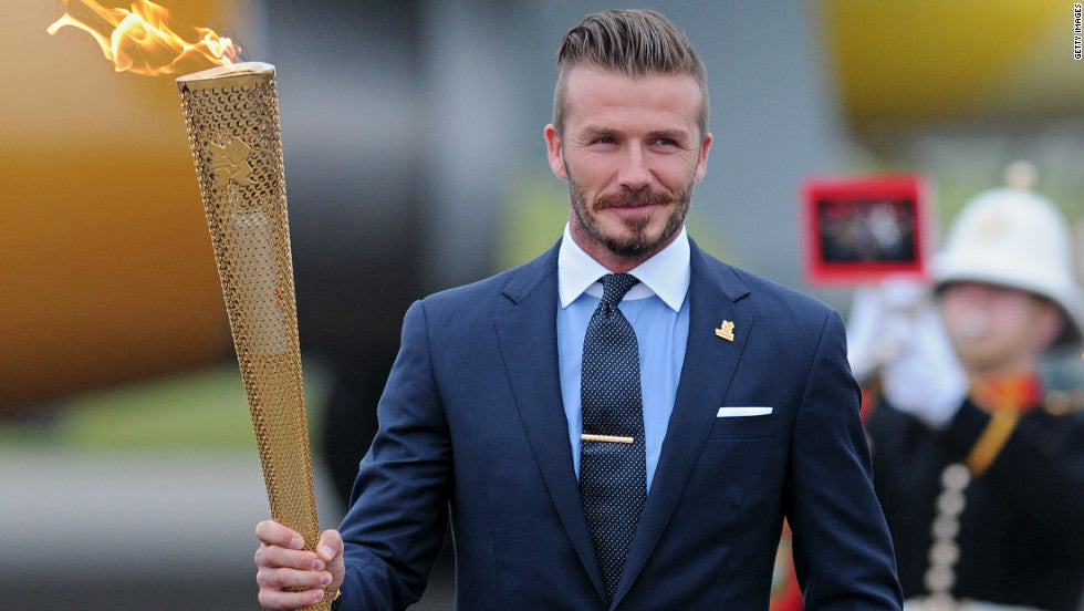 David Beckham, carrying the olympic torch, dons a classic English spread.