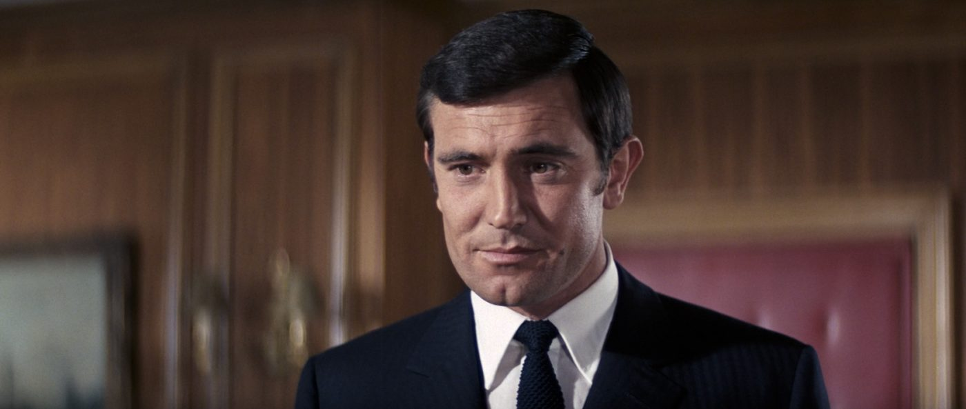 George Lazenby as James Bond, wearing a classic point collar shirt in On Her Majesty's Secret Service, 1969.
