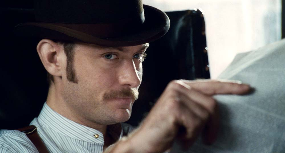 Jude Law as Dr. John Watson in Sherlock Holmes, wearing a collarless shirt.