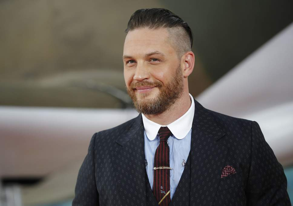 Tom Hardy sports a contrast club collar under a dark jacket.