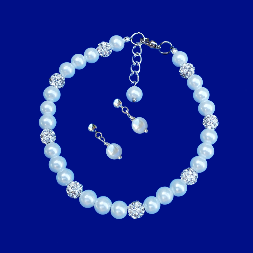 handmade pearl and crystal bracelet accompanied by a pair of pearl stud earrings