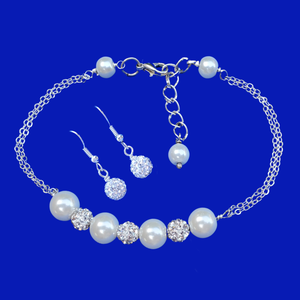 A handmade pearl and crystal bar bracelet accompanied by a pair of crystal earrings.