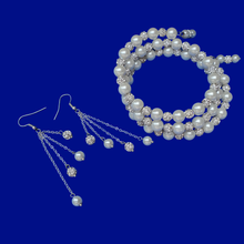 Load image into Gallery viewer, A handmade pearl and crystal expandable, multi-layer, wrap bracelet accompanied by a pair of multi-strand drop earrings.