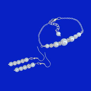A pearl and crystal bar bracelet accompanied by a pair of drop earrings.