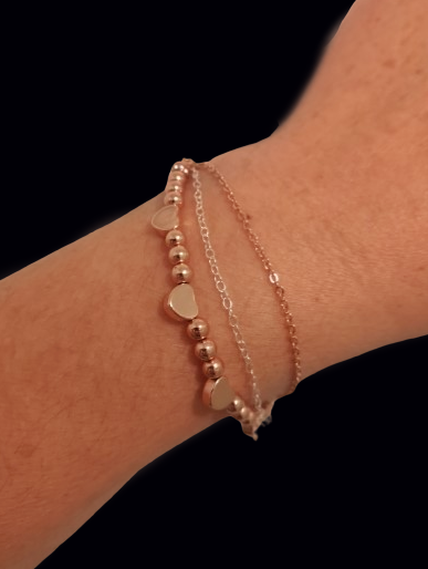A beautiful rose gold bracelet constructed with one strand of natural hematite beads combined with rose gold plated hearts. One strand of rose gold plated chain coupled with one strand of .925 sterling silver chain.