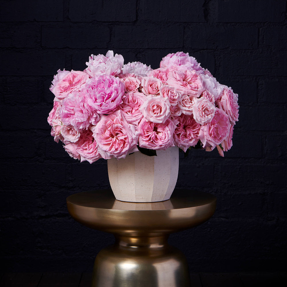 Pink O'Hara roses, pink majolica roses and pink peonies in a cement vase over golden pedestal.