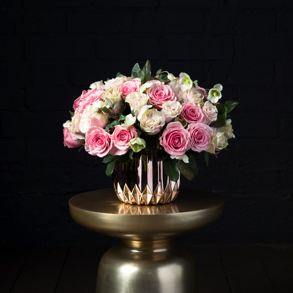 Geraldine and pink mondial roses paired with hellebores in a gold vase over golden pedestal.