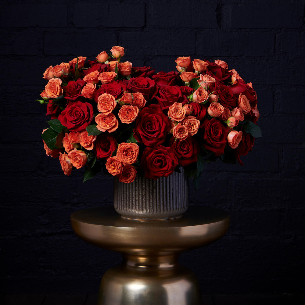 Blend of red and orange spray roses in a bronze vase over golden pedestal.