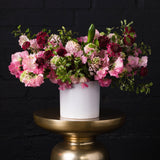 Raspberry scabiosa with fragrant pink hyacinth and variegated pink sweet peas in a white vase over golden pedestal.