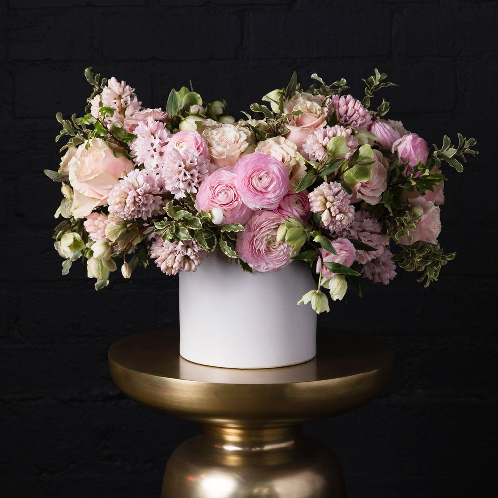 Pink hyacinth, pink mondial roses, pink ranunculus, helleborus and green accents in a white vase over golden pedestal.