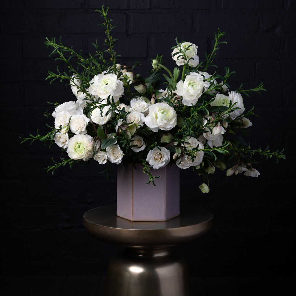 Blend of seasonal white florals in a purple vase over golden pedestal.