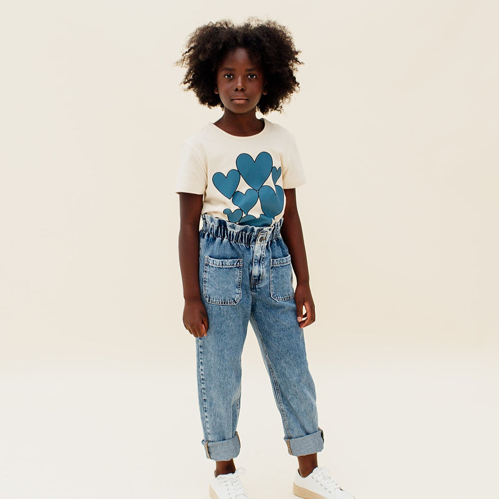 Girl CarlijnQ This Hearts t-shirt in créme brûlée is a short sleeved t-shirt with storm blue printed hearts on the front. 95% gots certified organic cotton.