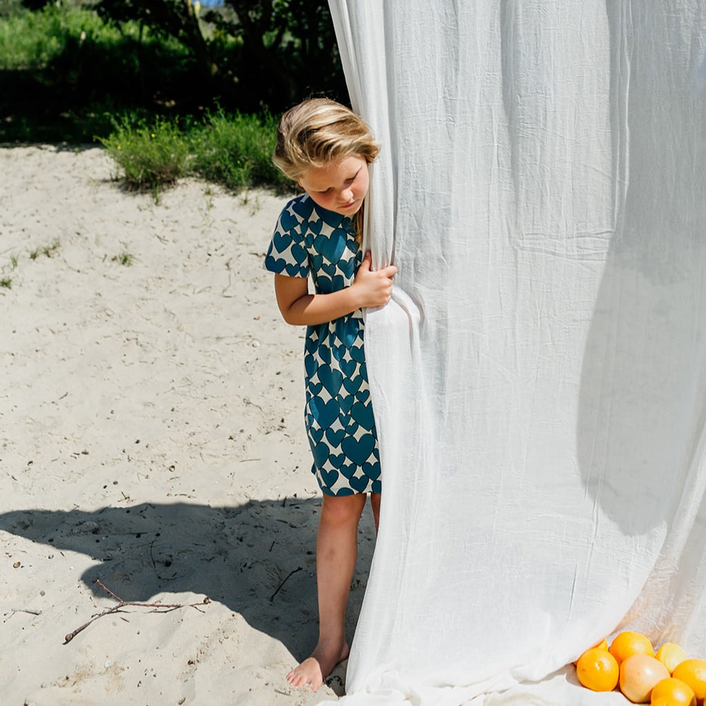 Girl wearing CarlijnQ Hearts dress short sleeve is a créme brûlée based dress with all over hearts print in colour storm blue. 95% gots certified organic cotton.