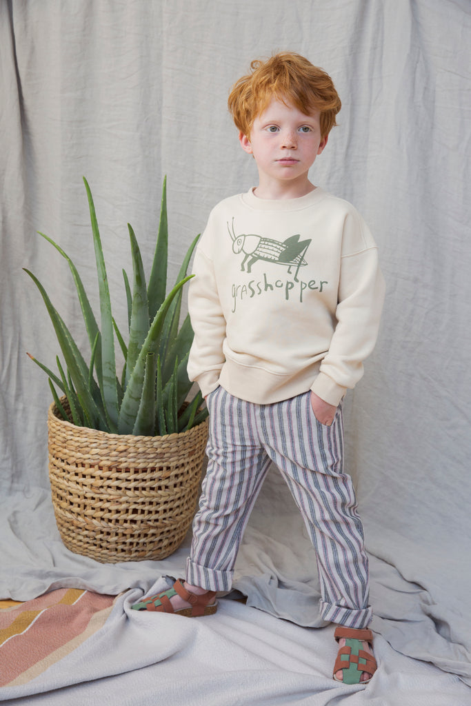 Boy wearing Ammehoela pants, perfect for warm weather. Ethically made in the EU. Gender neutral. Fit's true to size. Quality: 15% Linen / 35% Cotton / 50% Polyester.