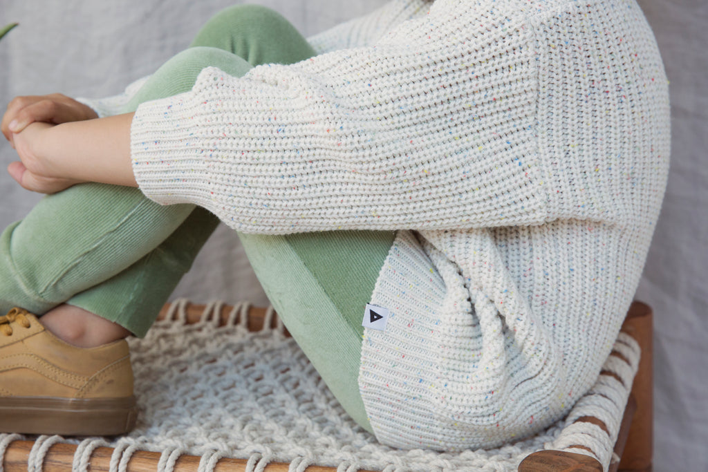 Girl wearing Ammehoela knit sweater in eggwhite with a subtle splash of colour. Ethically made in the EU. Gender neutral. 57% Cotton / 40% Acrylic / 3% Polyester. Closeup.