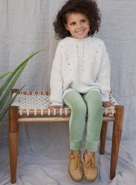 Girl wearing Ammehoela knit sweater in eggwhite with a subtle splash of colour. Ethically made in the EU. Gender neutral. 57% Cotton / 40% Acrylic / 3% Polyester.
