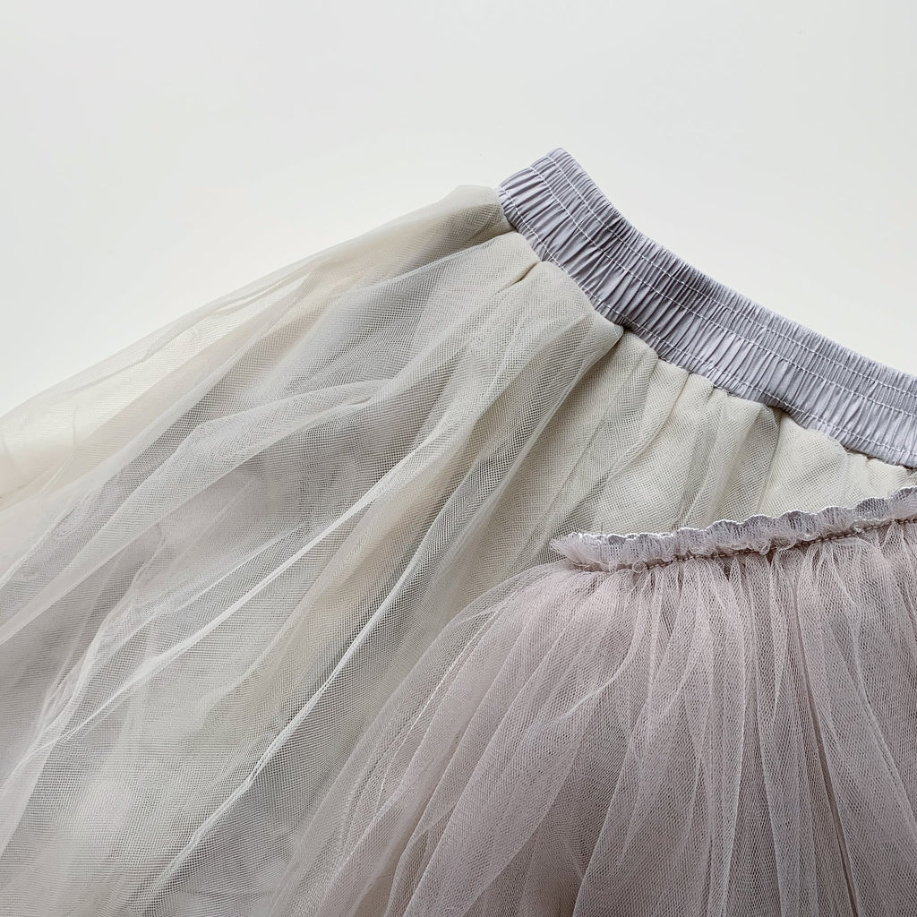Flat-lay of an adult and baby tulle skirts in grey.