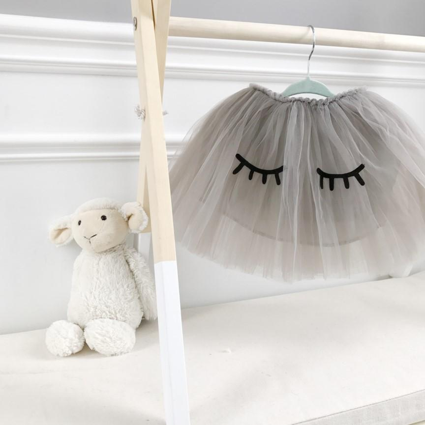 Bluish Baby Taylor Tutu Skirt in grey. It is made with three layers of silky soft tulle, a layer of cotton lining, and a velvety waistband that hugs your child's waist. The whimsical lashes are the perfect addition. Ethically made in China, and all the adorable details are hand-sewn in Markham, Ontario.